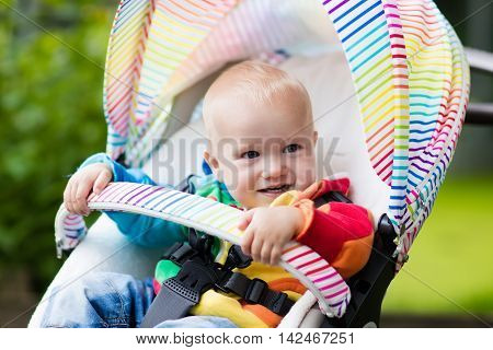 Baby boy in white sweater sitting in white stroller on a walk in a park. Child in colorful rainbow buggy. Little kid in a pushchair. Traveling with young kids. Transportation for family with infant.
