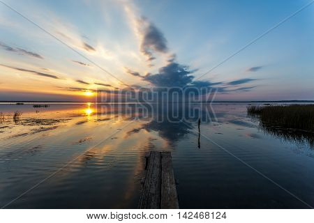 The wooden bridge from the coast of the lake reaches for beams of the summer sun setting for the horizon