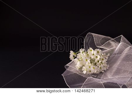 bouquet of small white flowers with a white veil on black textural background