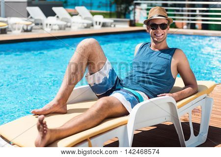 Full of joy. Positive delighted handsome man lying on the sun bed and smiling while resting near swimming pool