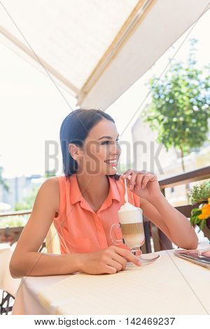 Happy young woman is drinking hot beverage in cafe with enjoyment. She is looking at city and smiling