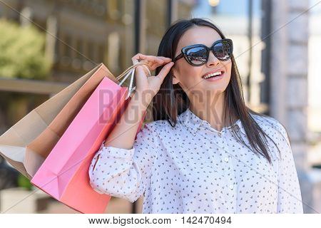 Joyful young woman is buying things in city. She is standing outdoors and holding packets. Lady is touching sunglasses and laughing