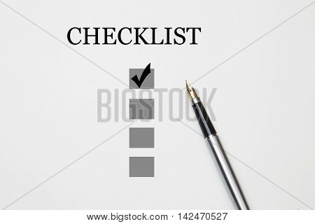 checklist with a ticked box and a pen