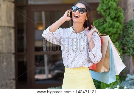 Pretty young woman is talking on mobile phone and smiling. She is standing on street and carrying shopping packets