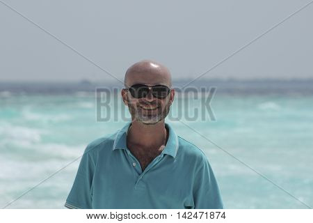 bald middle-aged man with a beard on the beach