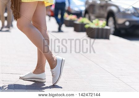 Close up of female legs standing on street