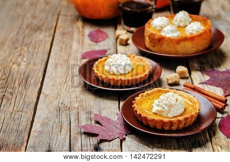 pumpkin pie decorated with whipped cream on wooden background