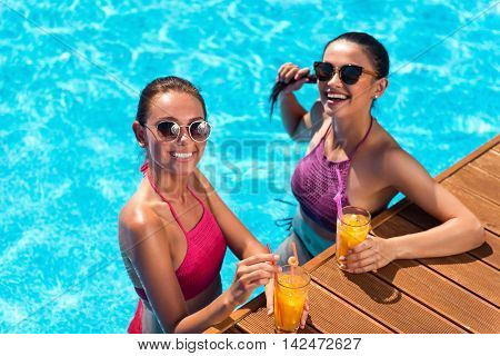 Share positivity. Overjoyed content friends standing in the swimming pool and expressing joy while drinking cocktails