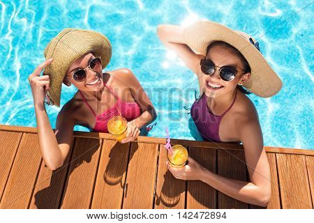On the edge of delight. Cheerful content smiling friends standing in a swimming pool and drinking cocktails while expressing joy