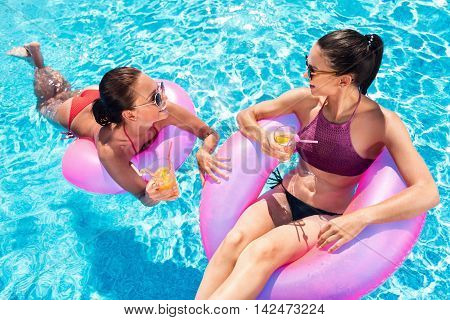 Active way of life. Cheerful content smiling friends swimming in a pool and sitting on the inflatable rings while drinking cocktails