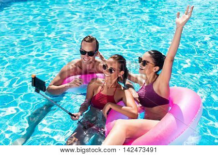 Endless jubilation. Cheerful content smiling friends relaxing in a swimming pool and having fun while making selfies