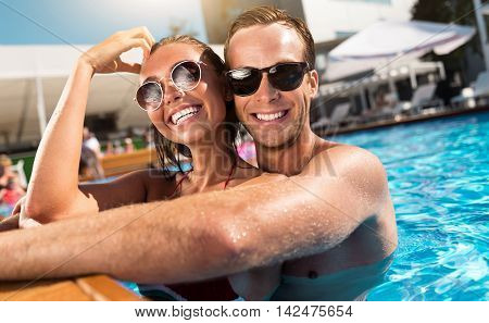 My beloved. Cheerful loving couple smiling and embracing while swimming in a pool