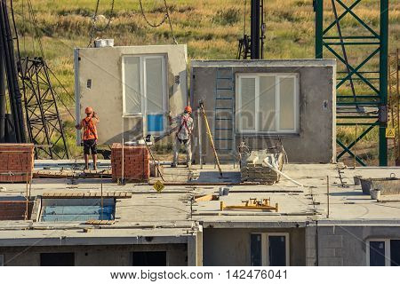 Worker setting up concrete panels during building construction
