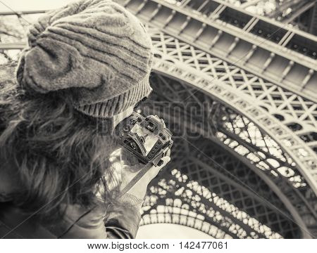 Young girl traveling and taken pictures Eiffel Tower, with photo camera.