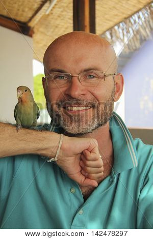 smiling bald man with a beard with a parrot on his hand