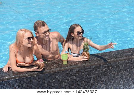 Look at that. Pretty girl is pointing finger forward and laughing. Her friends are looking there with interest. They are standing in pool and drinking beverage