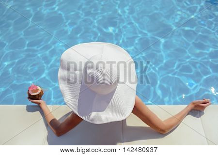 Top view of elegant young woman is relaxing in swimming pool and drinking cocktail. She is wearing big white hat