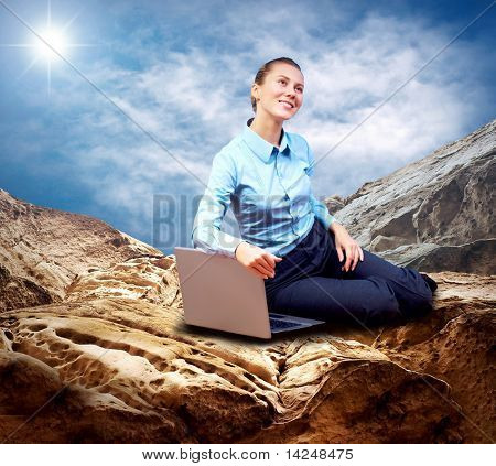 Happy Businesswoman seating with laptop on the mountain under blue sky