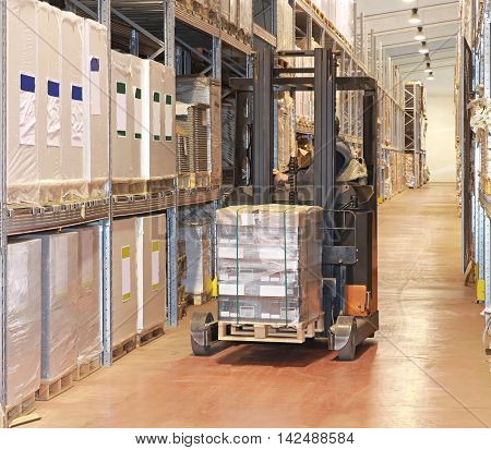 Loading Pallet With Forklift in Distribution Warehouse
