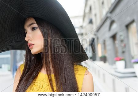 Pretty girl is walking on street with elegance. She is wearing big sunhat. Lady is looking forward with curiosity