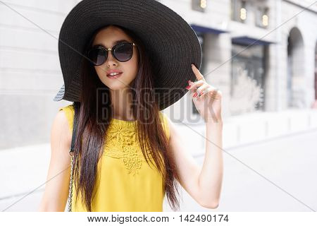 Flirty young woman is standing on street and touching her black hat. She is looking at camera and smiling