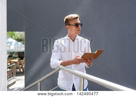 Smart young man is using tablet outdoors. He is standing on staircase and looking forward with seriousness
