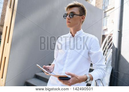 Confident young man is standing on stairs near building. He is carrying tablet and looking forward with anticipation