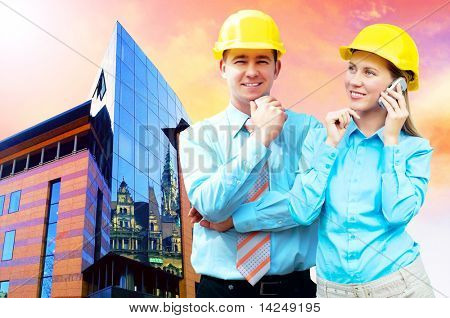 Young architects wearing a protective helmet standing on the building background