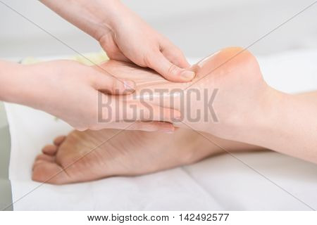 Close up of beautician hands massaging female heel at beauty salon