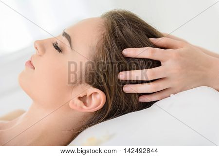 Young woman is getting massage at beauty salon. She is lying with relaxation. Masseuse is touching her hair gently