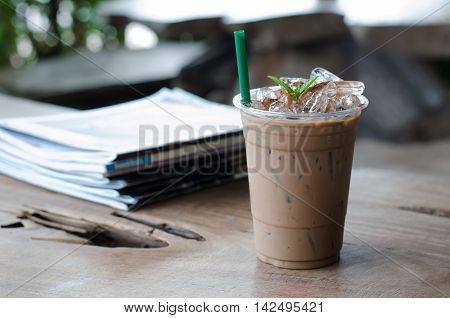 Ice peppermint mocha and book on wooden table