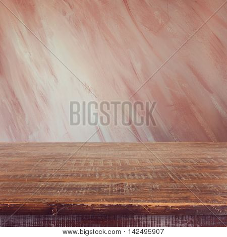 Empty wooden table over painted marsala color wall background