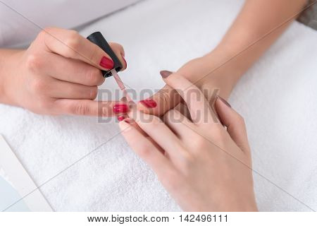 Close up of beautician hand doing manicure for young woman. She is applying pink varnish on her nail