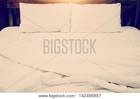 Messy white bed and pillow in the nigth