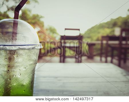 Close-up of a glass of ice kiwi soda with drop of water on wooden table with blurred view of chair sky and mountain in coffee shop surrounded by nature at Chiangmai Thailand