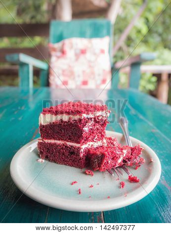 Cutting red velvet cake on green table with blurred chair in the morning at coffee shop surrounded by nature in Chiangmai Thailand (Vertical)