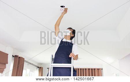 Single Asian Man Fixing Light At Home.