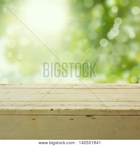 Nature background with empty wooden table over bokeh garden