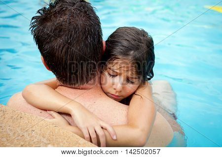 A young girl holds onto the neck of her father in a swimming pool. She is sad and pouting. It is a sweet father daughter image.