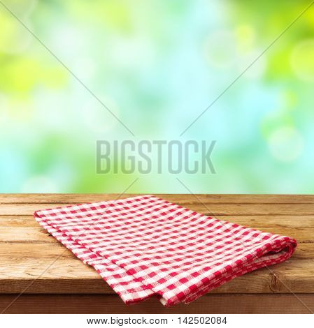 Empty wooden deck table with tablecloth over nature background