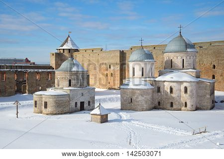 The old Church of St. Nicholas and Cathedral of the Assumption within the walls of the Ivangorod fortress on a march day. Ivangorod Russia
