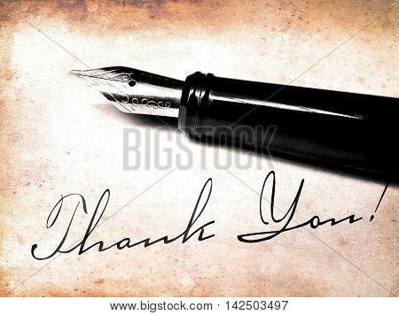 Fountain pen lying on an antique letter with thank you writing