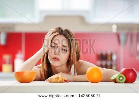 Woman looking guilty at croissant lying among fruits