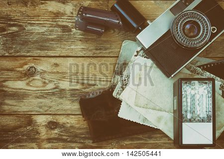 vintage camera film photographs flash on an old wooden table retro style
