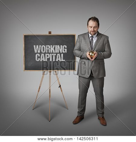 Working capital text on  blackboard with businessman and golden egg