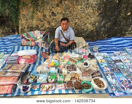 CHIANG RAI THAILAND - AUGUST 9 : horizontal photo of unidentified man selling herbs in a market at the Thai-Laos frontier on August 9 2016 in Chiang rai Thailand. This is one of travel attraction in Chiang Rai.