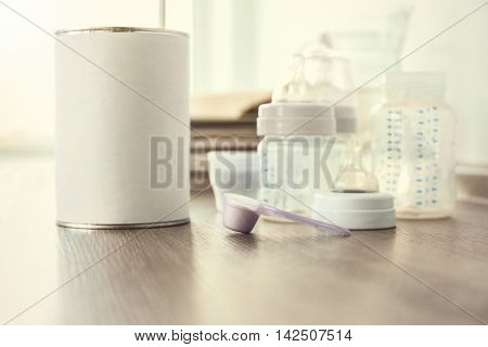 Baby milk formula in spoon on wooden table, closeup