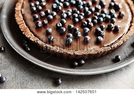 Delicious chocolate tart with blueberry on grey table, closeup