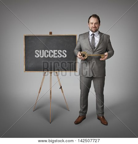 Success text on  blackboard with businessman and key