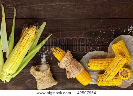 Cooked and raw corncobs on a dark wooden background. top view